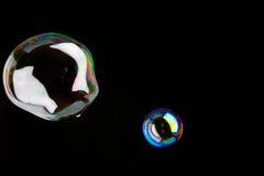Glänzende Seifenluftblasen vor einem dunklen Hintergrund Lizenzfreies Stockfoto