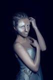 Glänzende silberne Dame in der Dunkelheit Stockfotografie