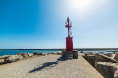 Glänzende Sonne über einem roten Leuchtturm in Alghero Stockbilder