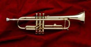 Glänzende Trompete auf rotem Veloursleder stockfoto
