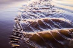 Glänzende tropische Seewelle auf goldenem Strandsand im Sonnenunterganglicht Lizenzfreies Stockfoto