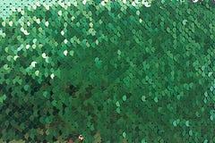 Glänzender grüner Hintergrund mit Goldrundenpailletten wie dem Endstück einer Meerjungfrau stockbilder