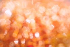 Glänzender orange Hintergrund mit dem bokeh sechseckig lizenzfreie stockfotos