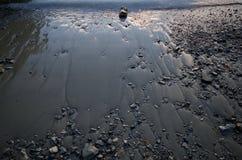 Glänzender Sand und Kies des Strandes und des plätschernden Meeres im Licht des frühen Morgens Lizenzfreies Stockbild