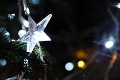 Glänzender Stern auf einem Weihnachtsbaum Stockfoto