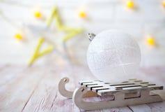Glänzender Weihnachtsball auf hölzernem Schlitten des Spielzeugs auf hellem bokeh Hintergrund mit goolden Stern Einladung des neu Lizenzfreie Stockbilder