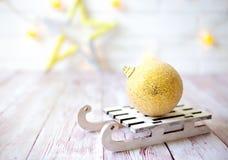 Glänzender Weihnachtsball auf hölzernem Schlitten des Spielzeugs auf hellem bokeh Hintergrund mit goolden Stern Einladung des neu Stockfoto