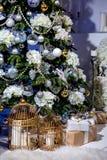 Glänzender Weihnachtsbaum verziert mit Bällen und Blumen, Geschenke und Kerzen in den Käfigen unter ihm im Wohnzimmer Ein Aufbau  stockfoto