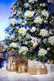 Glänzender Weihnachtsbaum verziert mit Bällen und Blumen, Geschenke und Kerzen in den Käfigen unter ihm im Wohnzimmer Ein Aufbau  stockfotos