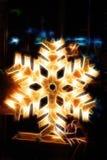 Glänzendes elektrisches Weihnachtsschnee-Flockensymbol, auf dunklem nächtlichem Hintergrund Lizenzfreies Stockbild
