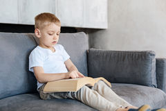 Glänzendes erstaunliches kreatives Kind, das ein Buch liest Stockfoto