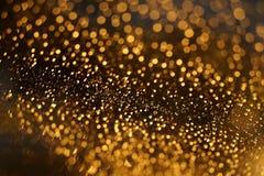 Glänzendes goldenes bokeh auf dem Fenster Stockfotos