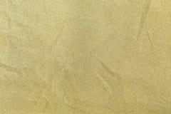 Glänzendes Papier des goldenen Funkelns wird für Weihnachtshintergrund, Feierkonzept zerknittert stockfotografie