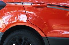 Glänzendes rotes Auto mit Reflexion des Parkhintergrundes stockfoto