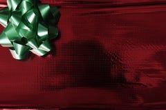 Glänzendes rotes Verpackungspapier mit grünem Bogen Lizenzfreie Stockbilder