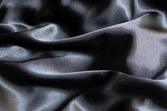Glänzendes schwarzes Gewebe mit Falten lizenzfreie stockfotos