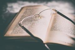 Gläser auf altem geöffnetem Buch Stockfoto