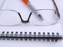 Gläser auf blocknote zwei Stockbild