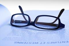 Gläser auf Buch Lizenzfreie Stockfotos