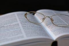 Gläser auf Buchseite Stockbilder