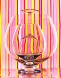 Gläser auf buntem gestreiftem Hintergrund Stockfotografie