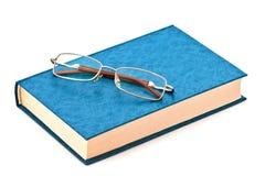 Gläser auf dem blauen Buch Stockfotos
