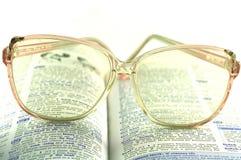 Gläser auf dem Buch Stockfotografie