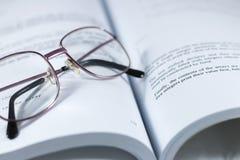 Gläser auf dem Buch Stockfoto
