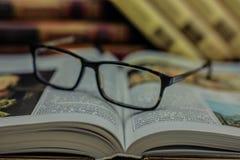 Gläser auf dem geöffneten Buch stockfotos