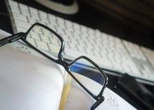 Gläser auf dem täglichen Klotz vor dem hintergrund des Computers Stockbild