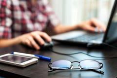 Gläser auf dem Tisch mit Handy und Studenten auf einem Hintergrund Lizenzfreie Stockfotografie