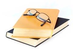 Gläser auf den alten Büchern Stockbilder