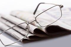 Gläser auf den Zeitungen Stockbild