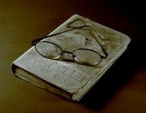 Gläser auf einem alten Buch Stockfotografie
