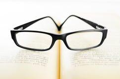 Gläser auf einem Buch Stockbilder