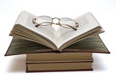 Gläser auf einem geöffneten Buch. Stockfotos