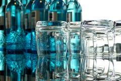 Gläser auf einem Glastisch mit Flaschen Wasser Lizenzfreies Stockbild