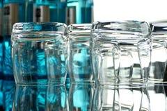 Gläser auf einem Glastisch mit Flaschen Wasser Stockfotografie