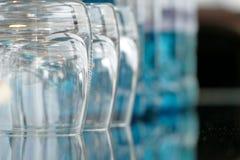 Gläser auf einem Glastisch mit Flaschen Wasser Lizenzfreie Stockfotografie