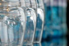 Gläser auf einem Glastisch mit Flaschen Wasser Lizenzfreie Stockfotos