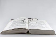 Gläser auf einem Lesebuch Stockbild