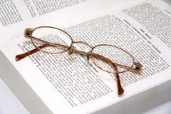 Gläser auf einem medizinischen Buch Stockfoto