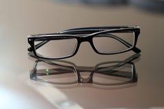 Gläser auf einer Glastabelle Stockbild