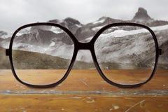 Gläser auf Holztisch und Winterlandschaft Lizenzfreies Stockfoto