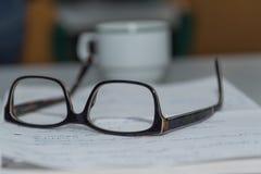 Gläser auf Manuskripten - Nahaufnahme stockbild