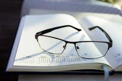 Gläser auf Notizblock Stockfotografie
