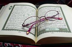 Gläser auf Quran Stockbild