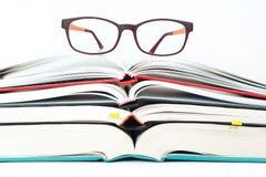 Gläser auf Stapel offenen Büchern Stockfotos