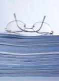 Gläser auf Zeitschriften-Stapel stockfotografie