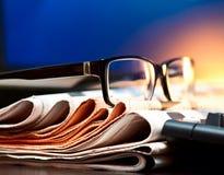Gläser auf Zeitungen Stockfotografie